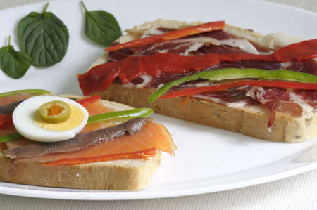 Tasty bread slices with salmon and ham photo