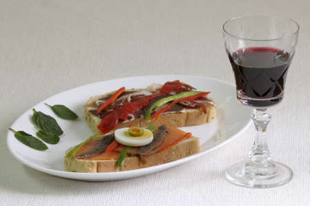 Tasty bread slices with salmon and ham. And glass of red wine photo