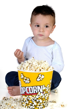 Adorable child eating popcorn on white background photo