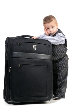 Child with luggage, waiting for departure Stock Photo