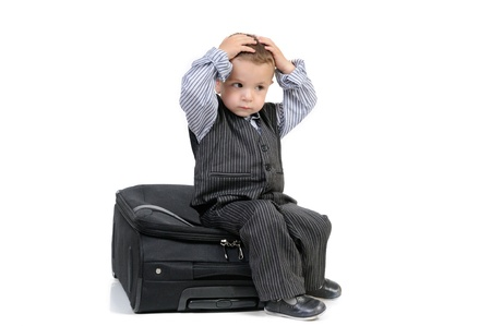 Little traveler boy with a suitcase. Isolated over white background