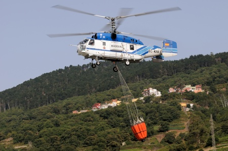 SANTA CRUZ DE TENERIFE, AUGUST 3  Fire fighting Helicopter Kamov KA-32a-11BC, with bambi basket, during a fire fighting in the bush  August 3, 2013, Tenerife  Canary Islands  Spain