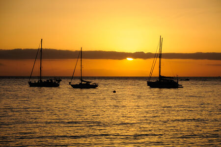 Sunset on a beach in Tenerife and silhouette of sailboats
