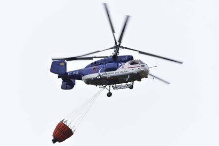 SANTA CRUZ DE TENERIFE, OCT 12: Fire fighting Helicopter Kamov KA-32a-11BC, with bambi basket, during a fire fighting in the bush. October 12, 2017, Tenerife (Canary Islands) Spain. Editorial