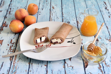 Oatmeal crepe with jam and fresh cheese.