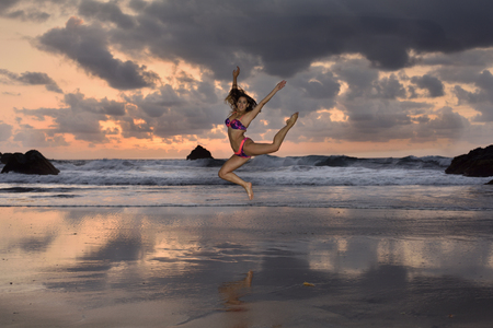 A beautiful girl jumping on a lonely beach