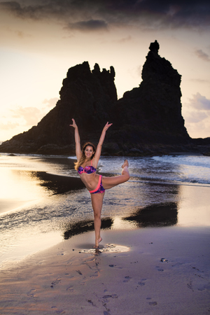 Attractive girl doing a ballet pose on the beach Stock Photo