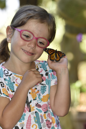 Small girl holds in her hands a monarch butterfly that has just been born