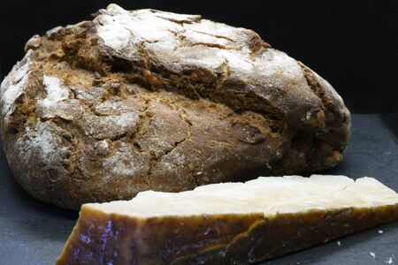 Loaf of freshly baked bread and a wedge of cured cheese