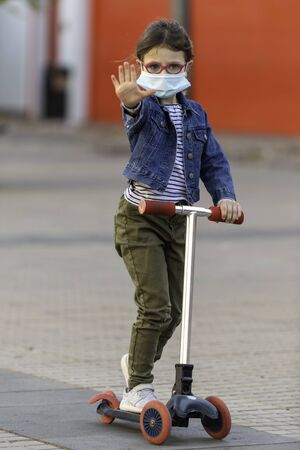 Little European girl, plays with her kick scooter protecting herself against the covid-19