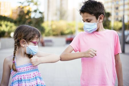 Children greeting each other during the coronavirus pandemic Stock Photo