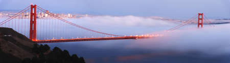 Fog rolls the Golden Gate Bridge at dusk. The city of San Francisco is in the background. Panoramic composition.