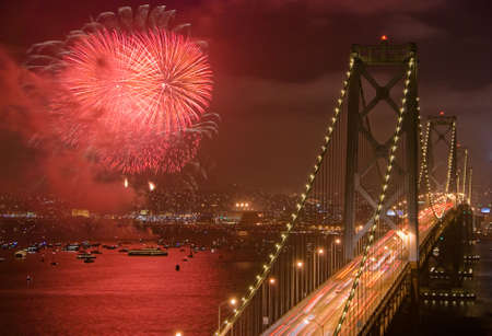 Fireworks light up the city next to the Bay Bridge, the famous San Francisco landmark.