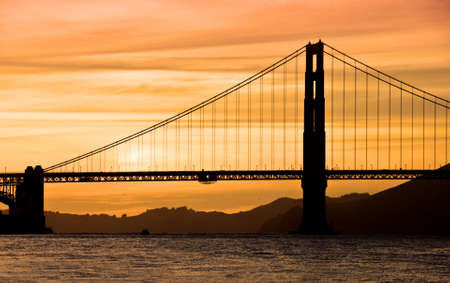 Silhouette of the Golden Gate Bridge at sunset.  Stock Photo