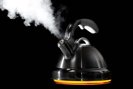 boiling pot: Tea kettle with boiling water on black background. Heater glow under the tea kettle.  Stock Photo