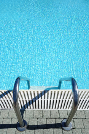 the entering: View of a ladder for entering into a crystal clear blue swimming pool water