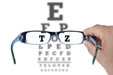 examen de la vista: Mano que sostiene los vidrios y la lectura de la visión del ojo prueba gráfica en blanco Foto de archivo