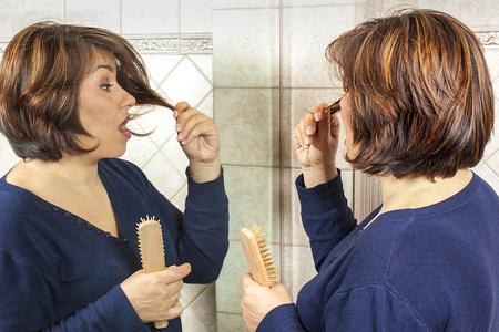 disapprove: Woman negatively surprising at mirror looking at her split ends Stock Photo