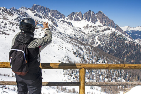 breath taking: Back View of young skier man taking video or shot with smartphone of dolomites