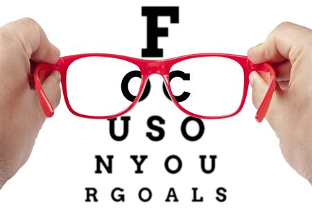focus on: Red spectacles focusing on text focus on your goals arranged as eye chart test Stock Photo