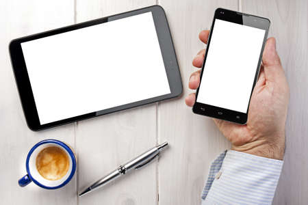blank tablet: Top view businessman holding smartphone next to tablet with blank screen on white wooden table