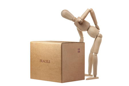 heavy risk: Wooden Mannequin having an accident carrying box isolated Stock Photo