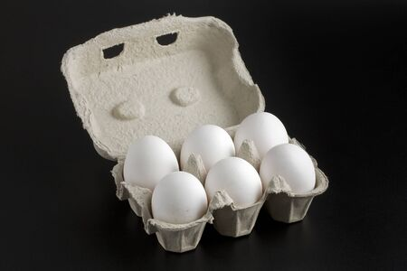 ailment: Six whole white eggs in a cartoon container open on black background