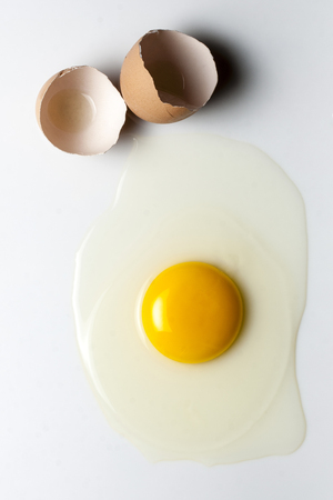 egg white: Top view splattered broken egg and egg shell Stock Photo