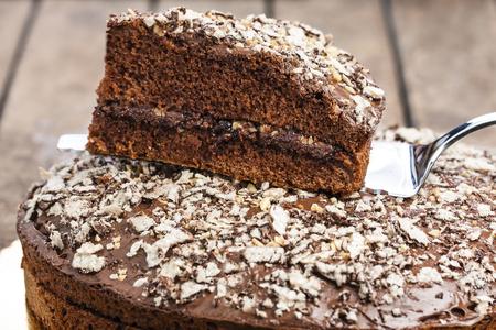 caloric: Closeup chocolate dessert slice on silver cake slice on rustic wooden table Stock Photo