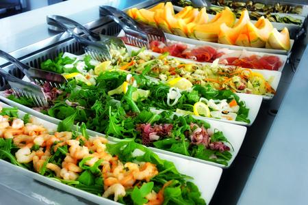 Bandejas de acero rellenos de deliciosa comida en el restaurante de autoservicio