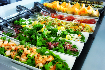 buffet lunch: Steel trays filled with delicious food at self service restaurant Stock Photo