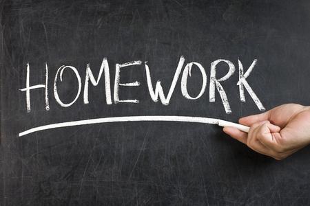 underscore: Teacher male hand with white chalk handwritten homework underlining text on dirty blackboard Stock Photo