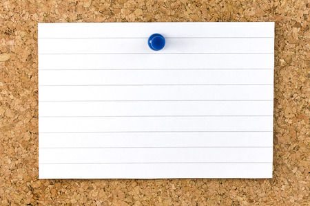 Blank white horizontal striped sheet fixed on cork board with a small blue thumb tack