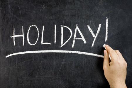 underscore: Hand with white chalk handwritten holiday underlining text on dirty blackboard Stock Photo