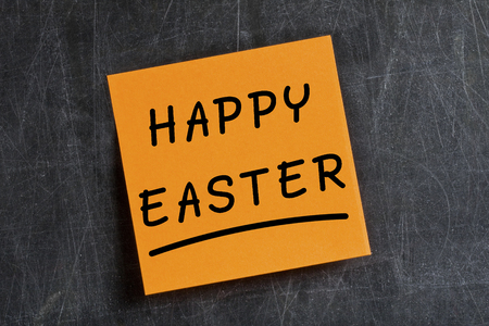 affixed: Handwritten text Happy Easter on orange postit glued on dirty blackboard Stock Photo