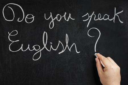 Do you speak Inglese vraag handgeschreven op bord gebruikt door mannelijke hand met wit krijt