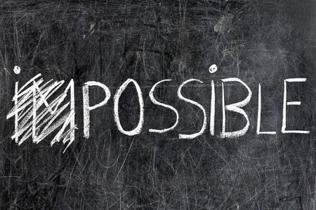 Impossible Becomes possible handwritten with white chalk on blackboard dirty 写真素材