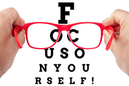 egocentric: Red spectacles focusing on text focus on yourself arranged as eye chart test