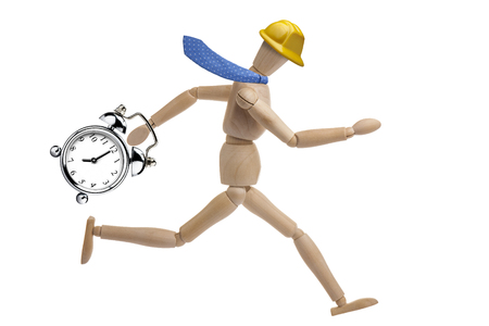 Wooden businessman mannequin with helmet running holding vintage clock alarm isolated