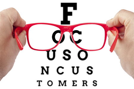 testing vision: Red spectacles focusing on text focus on customers arranged as eye chart test