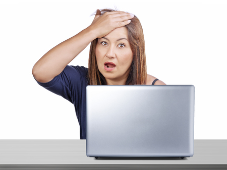 forgotten: Worried woman working at desk with laptop gesturing forgotten something or regret for mistake isolated Stock Photo