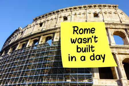 affixed: Idiom Rome wasnt built in a day on large postit affixed on Colosseum in Rome