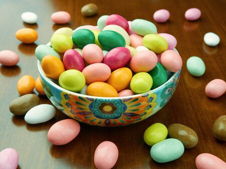 Bowl filled up with colored sugared almonds on the table Stock Photo