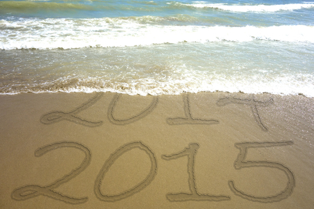 Waves covering inscription 2014 on a beach sand - new Year 2015 is coming concept