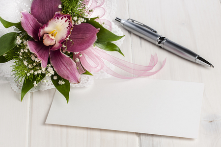 Blank white card on white wooden table next to orchid and silver ballpoint