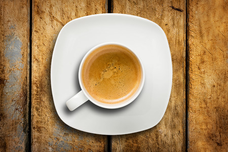 Top view of white cup of espresso coffee with saucer on wooden rustic table
