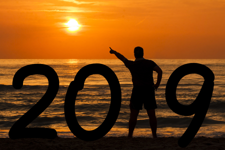 Man Silhouette forming year 2019 pointing out sun at sunrise at sea Stock Photo