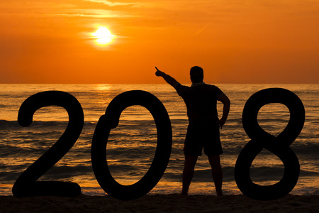 Man Silhouette forming year 2018 pointing out sun at sunrise at sea