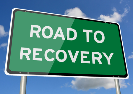 Road to recovery signpost against blue sky