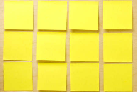 Blank well-ordered square yellow postit notes affixed on a wooden board